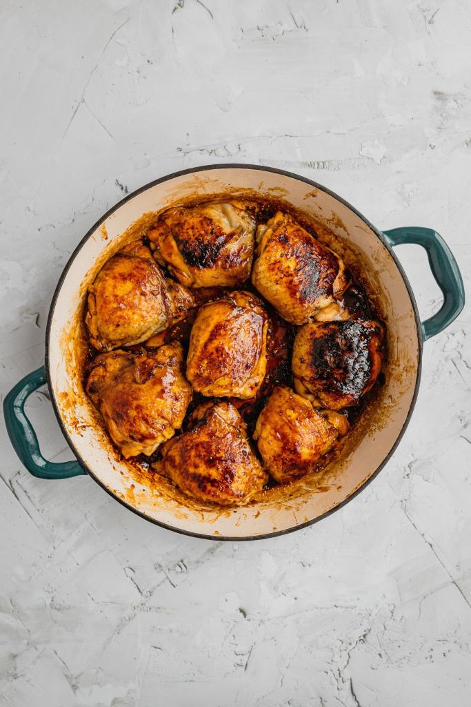 Seared chicken thighs in a shallow Dutch oven.