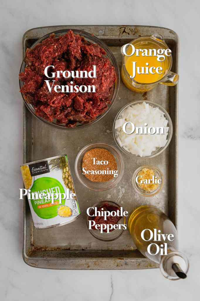 All the ingredients for ground venison tacos are in various glass bowls and measuring cups on a rimmed baking sheet.