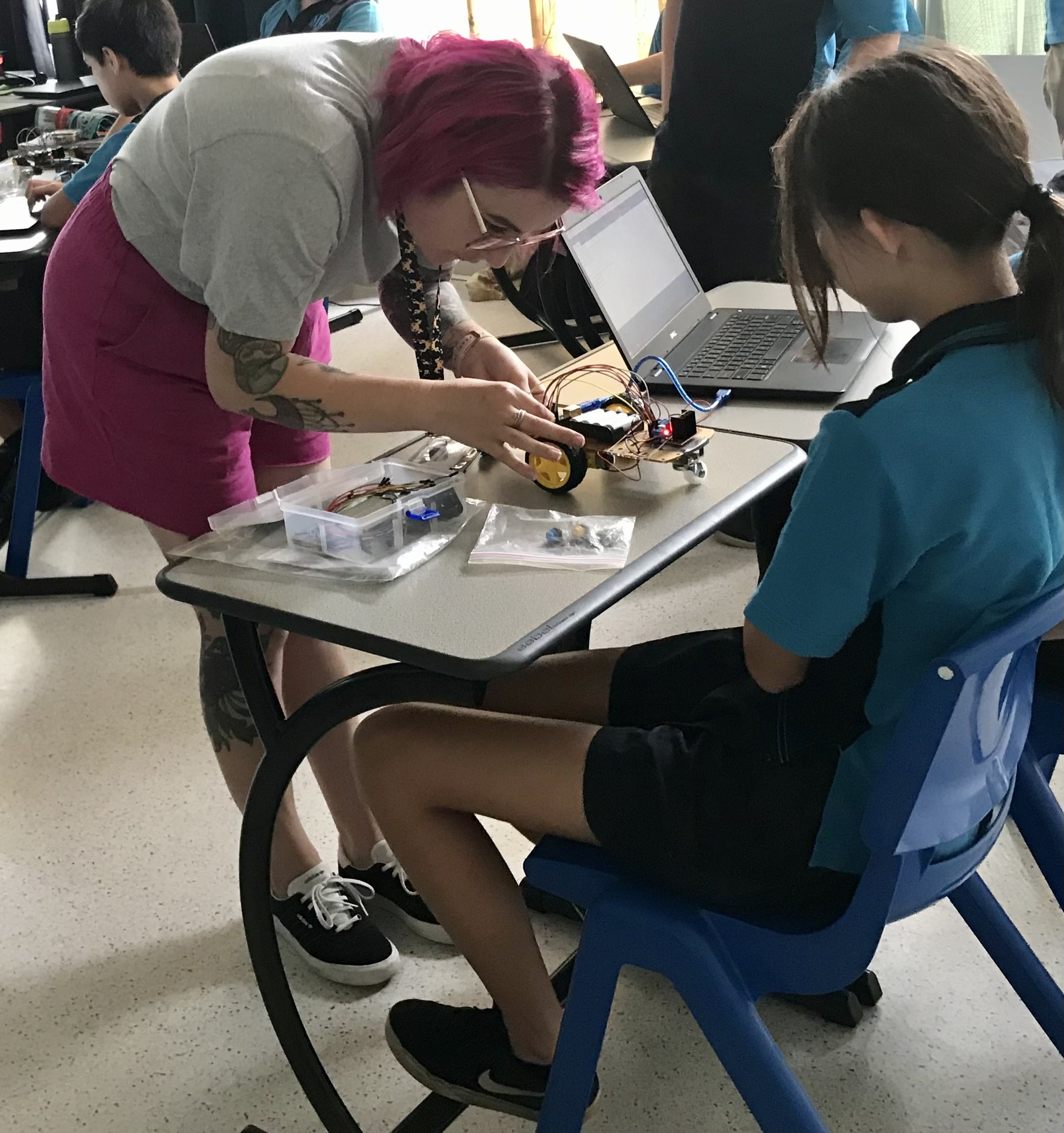 A pre-service teacher helps a student with their project - a small electronic car