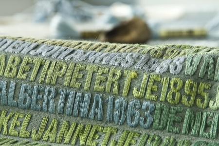 De Verdronkenen (2003-2008). Detail van het werk in wording. met een lederen vingerhoeje, de DMC-garens en aantekeningen van de kunstenares op de rand van het doek.Vijf panelen met de namen van alle 1836 slachtoffers van de Watersnoodramp van 1 februari 1953. Monumentaal werk van Miep van Riessen in acryl en garens op doek - 134 x 236,8 cm. StichtingMiepvanRiessen foto © Jan van de Ven  4021x2680 pixels