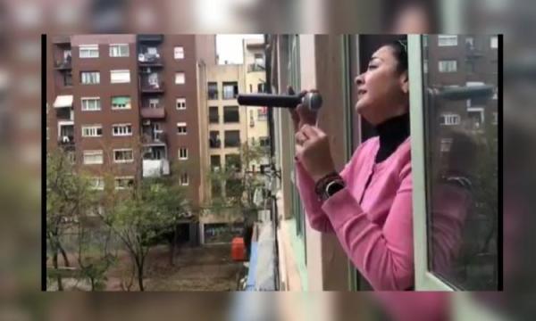 Mexicana canta y anima desde su ventana en Barcelona, España