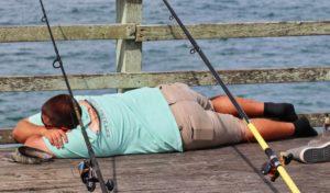pêcheur patient qui dort allongé sur des planches