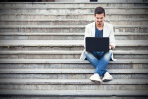 man sitting on stairs, working on laptop