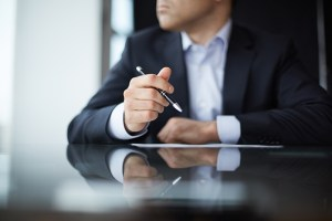 Find clients through branding - Image: businessman holding a pen