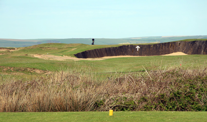 The tee shot on hole 4 on Royal North Devon is over the huge bunker. The arrow is painted on the wooden side of the bunker, telling you where to aim. This is Englands oldest golf club, founded 1864.  (Photo: The Migrant Golfer)