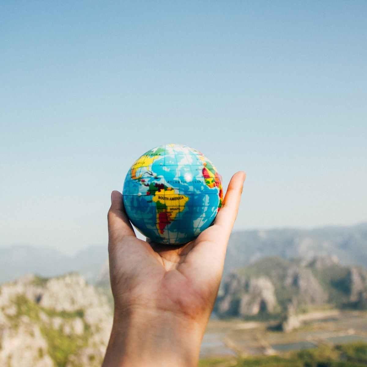 person holding world globe facing mountain