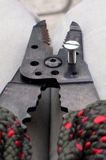 Wire cutters cutting a bolt