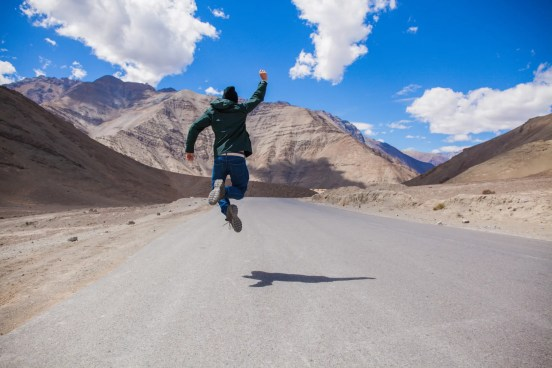 Extremely happy young male tourist jumping on country road with giant mountains behind