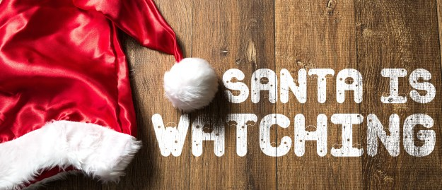 Santa is Watching written on wooden background with Santa Hat