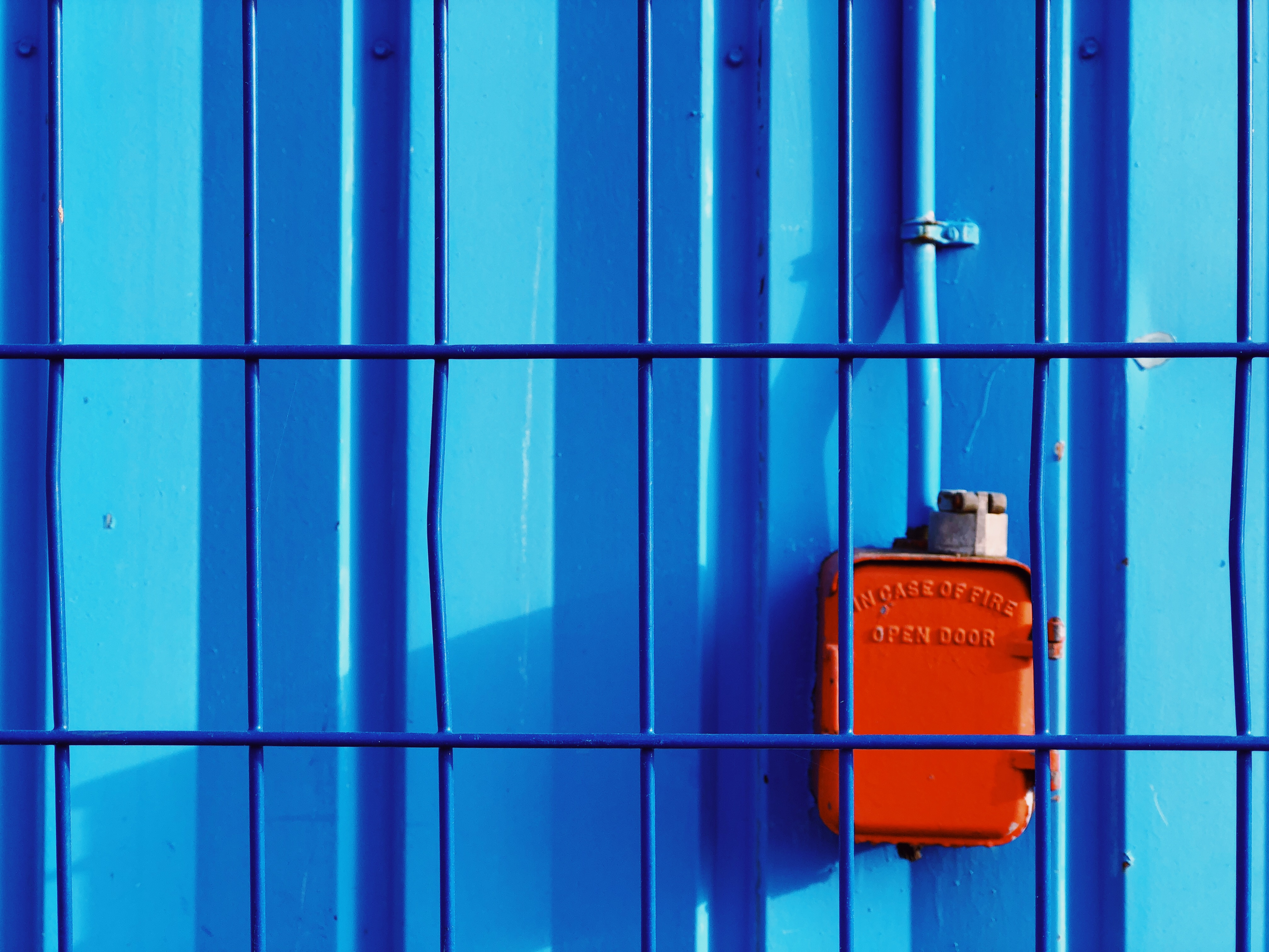 A photograph depicting Old Coast Guard Building Fire Box Through Fence