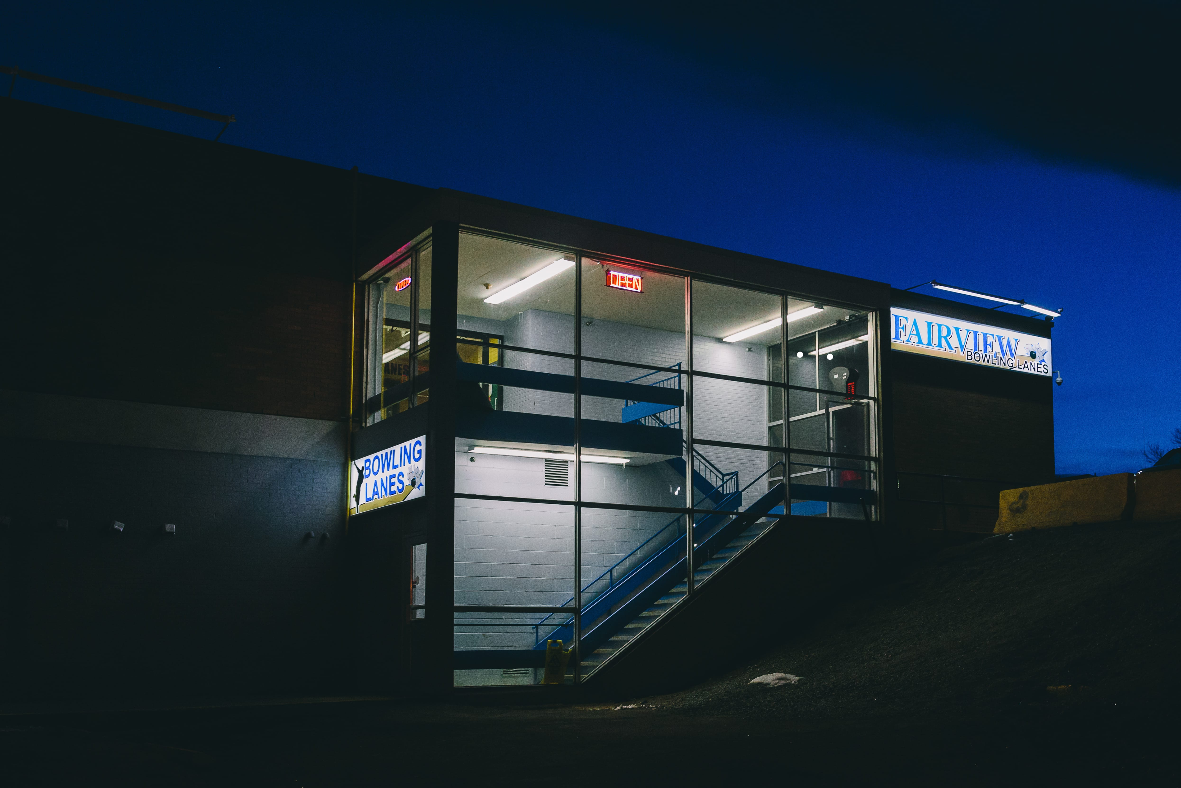 A photograph depicting Fairview Bowling Lanes Entrance at Night