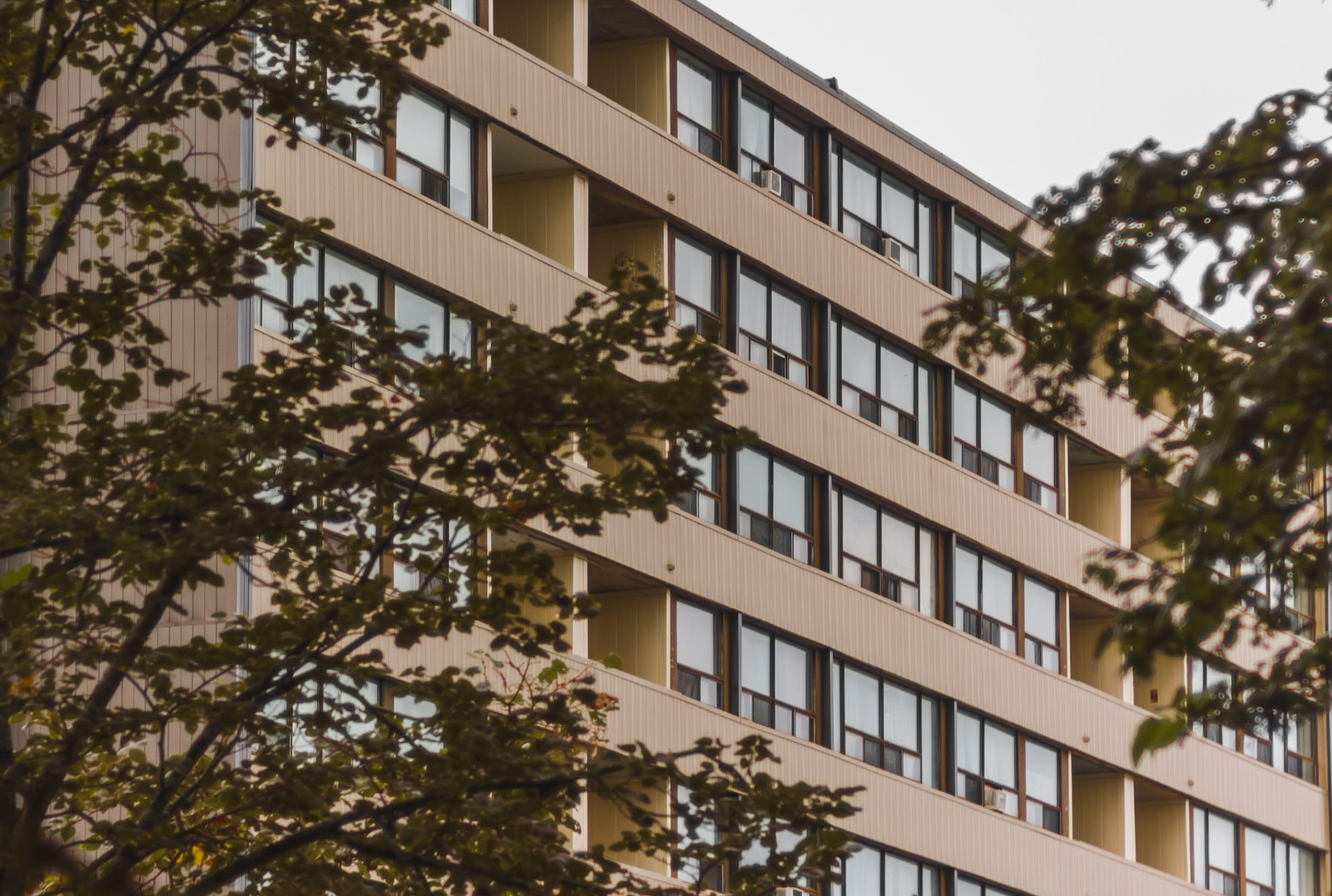 A photograph depicting Prince Edward Square Apartments Through Trees
