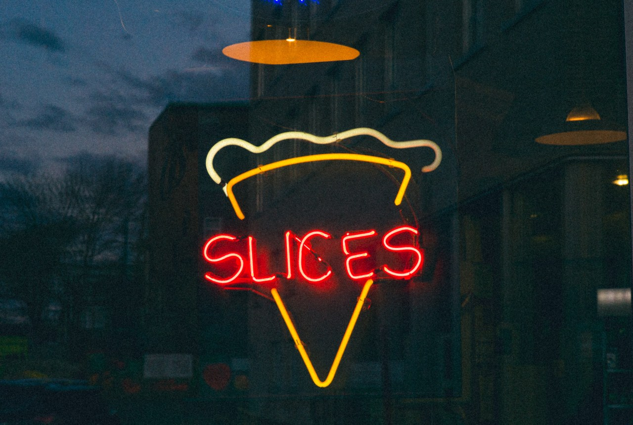 A photo of Pizza slices neon sign at Julius in Saint John