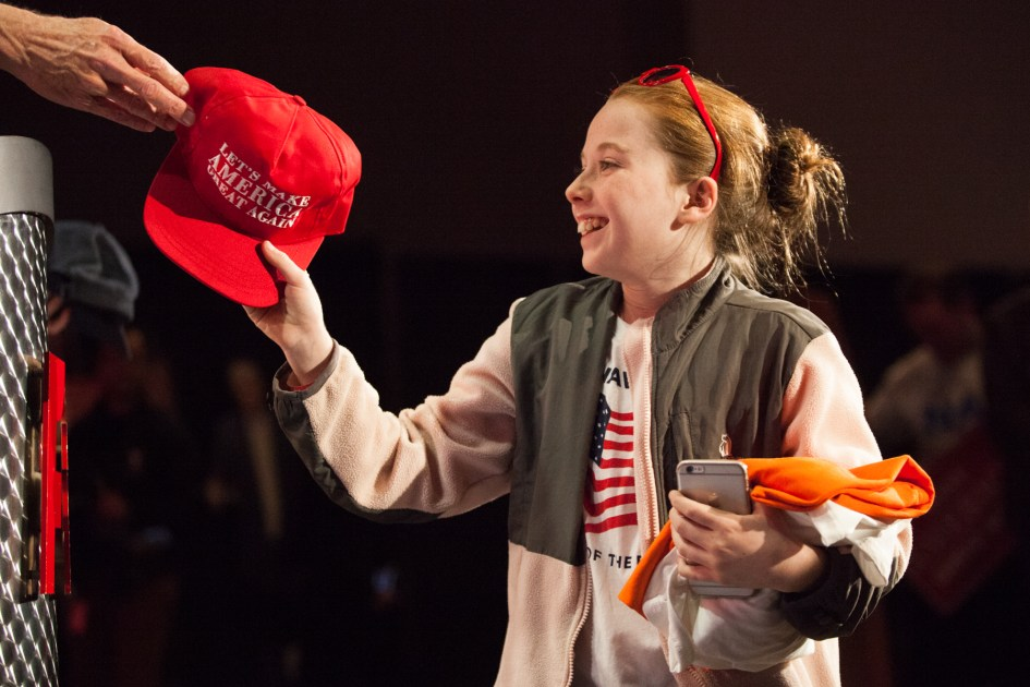 """Braintree, MA – Nov. 8, 2016 – A young audience member receives a free """"Make America Great Again"""" hat after correctly answering a trivia question at the Massachusetts Trump-Pence Campaign victory party. Trump supporters gathered at the F1 Boston race track to cheer on their nominee as he was elected 45th president of the United States."""
