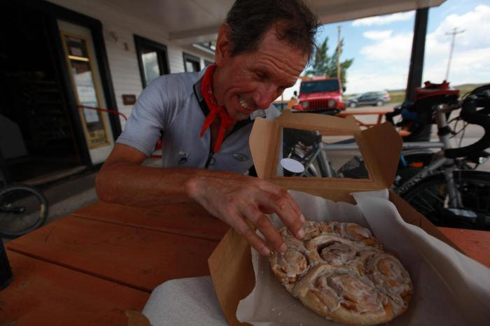 "Terry dives into our ""lunch"" a freshly baked box of six cinnamon rolls. --Crowheart, WY"