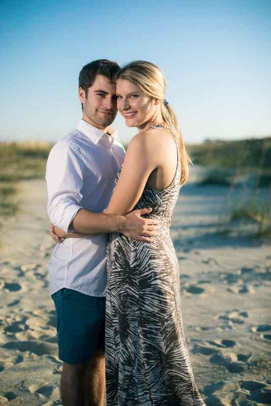 engaged couple hugs on tybee island beach