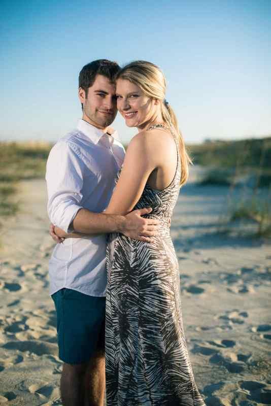 engaged couple hugs on tybee island beach