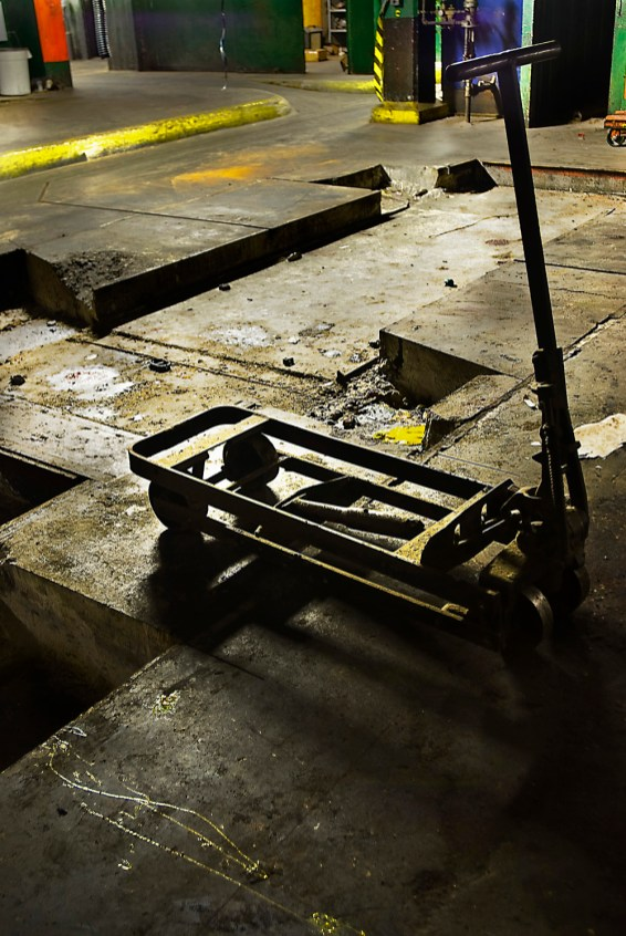 A single handtruck sits alone, possibly untouched for years in the basement press room.