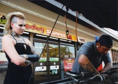 Frank Manfredonia, a TEC Equipment parts specialist helps Kayla Blackwell, artist at Invictus Tattoo Studio, in the parking lot of a 7-11 on Wells and Second streets. Photo by Mike Higdon