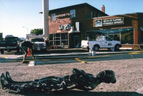 Black mannequin on the ground in front of Simple Ice Cream Sandwiches and Visionary while Joe C. Rock paints the asphalt with Battle Born Nevada, construction workers build the Visionary and Jessica Schneider watches in the background. Photo by Mike Higdon