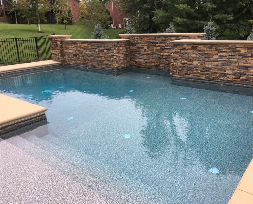 New Pool Installation with Concrete Deck and Stone Wall Feature - close up