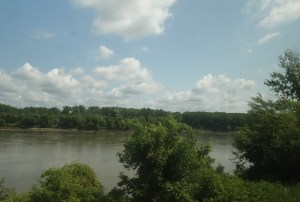 A view of the Missouri River taken from the Amtrack River Runner. Blue skies, puffy white clouds and trees lining the river