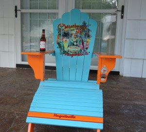 photo of a aqua blue and orange Jimmy Buffett Adirondack chair with a bottle of Budweiser sitting on the left armrest