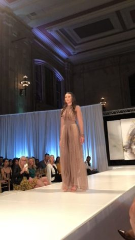 Emma Pound on the runway of KC Fashion Week. She is wearing a long gown. I'm sorry but that's about all I know to say.