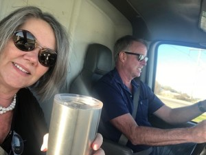 Lee and Mike Pound in the front seat of a U-Haul truck. Lee is on the left and is holding up a drink cup and smiling. Mike is driving the U-Haul and not smiling
