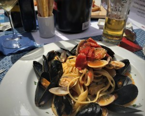 A picture of a plate of pasta with clams. Bright pasta covered with opened black shelled clams topped with tomatoes