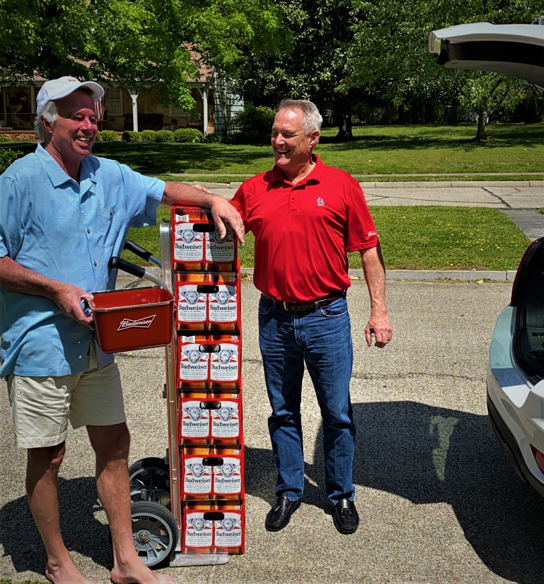 A picture of Mike Pound and Alan Beaver. Between the two of them is a stack of six, 20-packs of bottled budweiser