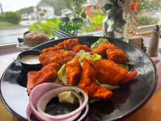 Hand-battered, boneless chicken tenders tossed in buffalo sauce; placed atop a vibrant, colorful salad with crisp iceberg, red onion slices, shredded carrots, and tomatoes