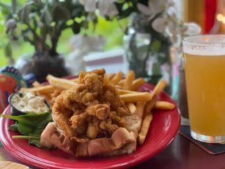 Fried clams with bellies packed into a buttery, grilled roll with tartar and fries on the side