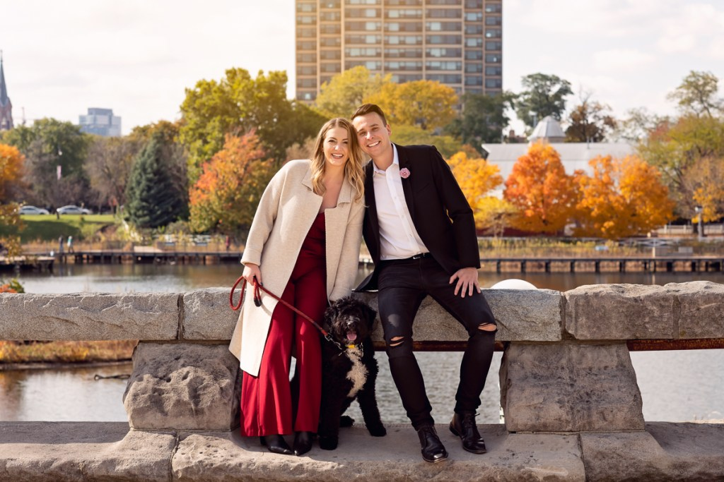 An engagement session for an engaged couple with a black dog in Lincoln Park in the fall by a wedding photographer Mila Craila Photography