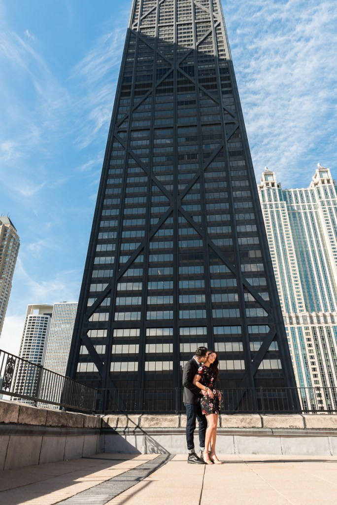 An engagement session for an engaged couple near Hancock Building in downtown Chicago in the fall by a wedding photographer Mila Craila Photography