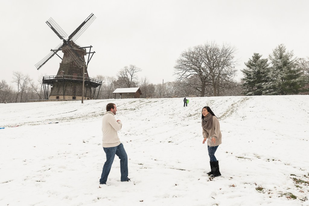 An engagement session for an engaged couple playing snow balls at the windmill at Fabyan Forest Preserve in the winter by a wedding photographer Mila Craila Photography