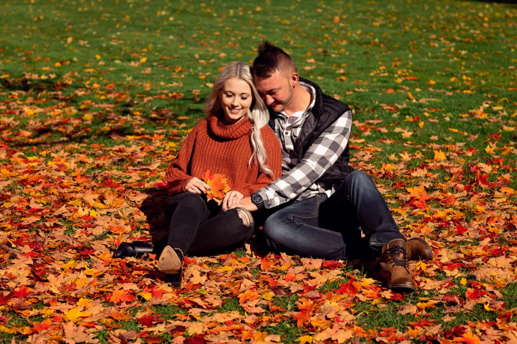 An engagement session for an engaged couple sitting on the ground at Cantigny Park in Wheaton in the fall by a wedding photographer Mila Craila Photography