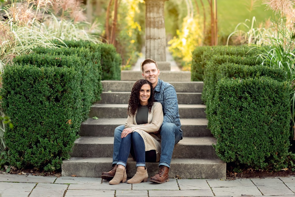 An engagement session for an engaged couple sitting on stairs at Fabyan Forest Preserve in the fall by a wedding photographer Mila Craila Photography