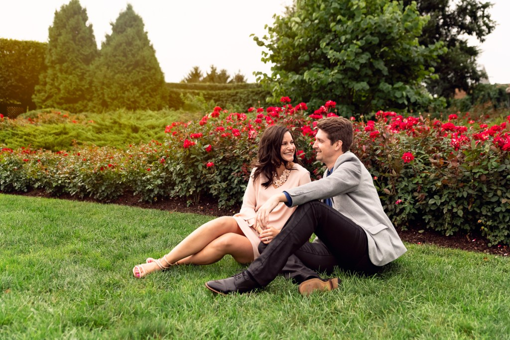 An engagement session for an engaged couple sitting in the rose garden at Chicago Botanic Garden in the summer by a wedding photographer Mila Craila Photography
