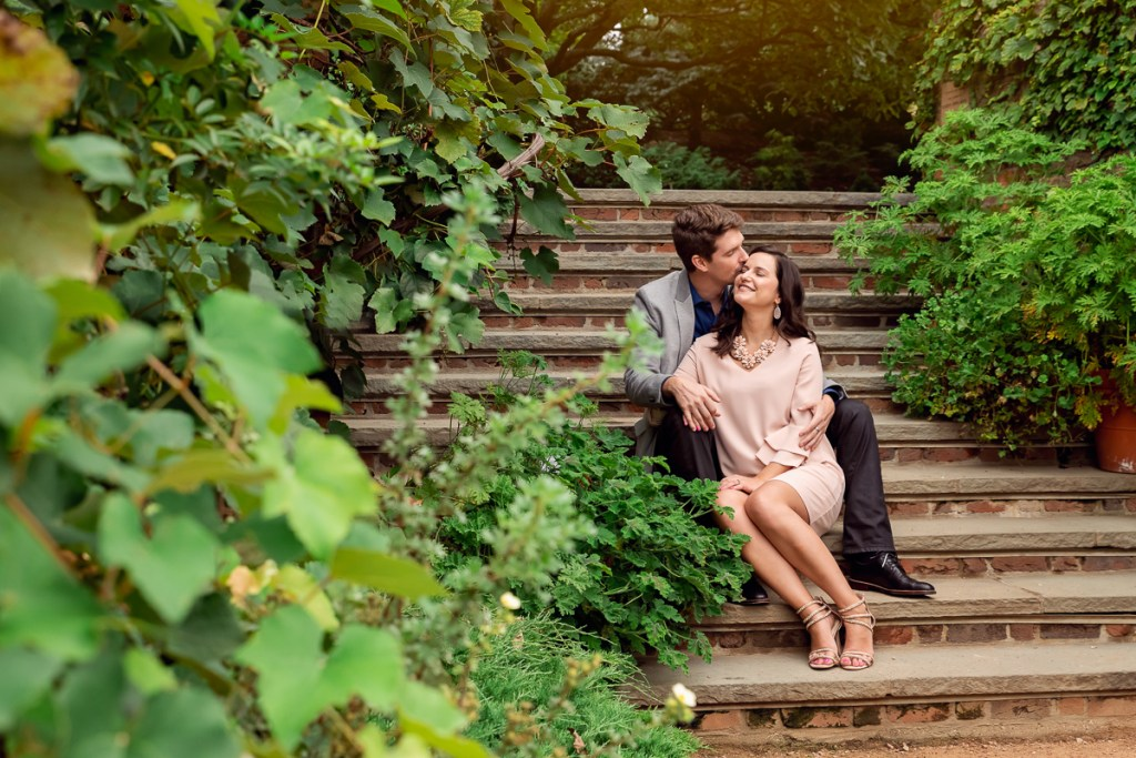 An engagement session for an engaged couple sitting on the stairs at Chicago Botanic Garden in the summer by a wedding photographer Mila Craila Photography