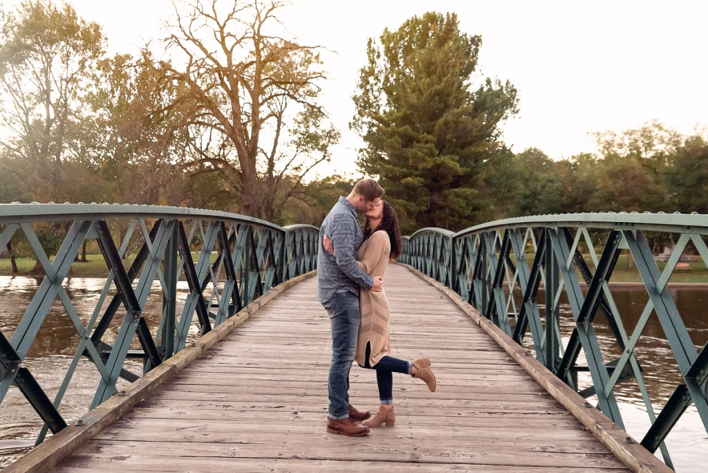 An engagement session for an engaged couple kissing on a bridge at Fabyan Forest Preserve in the fall by a wedding photographer Mila Craila Photography