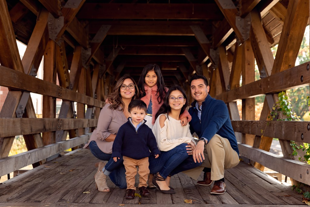 Family session for a family with three kids on the bridge on Naperville Riverwalk by family photographer Mila Craila Photography