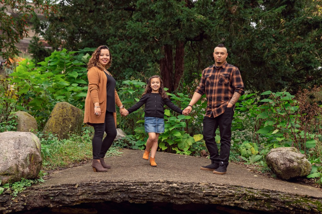 Family session for parents and a young daughter standing on a big stone at Fabyan Forest Preserve in Geneva by family photographer Mila Craila Photography