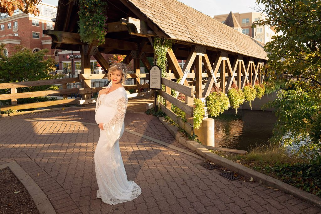 A maternity session for a pregnant woman in a white dress near the bridge on Naperville Riverwalk by a maternity photographer Mila Craila Photography