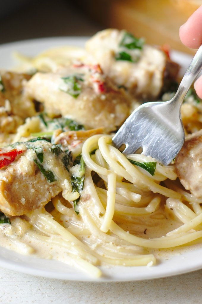 Tuscan Chicken Pasta - A rich and creamy chicken pasta ready in less than 30 minutes! Spinach, sundried tomatoes, chicken, and pasta topped with a cream-based sauce.  Perfect with parmesan on top!