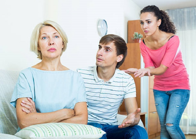 Frustrated woman watching how adults trying to reconcile with her