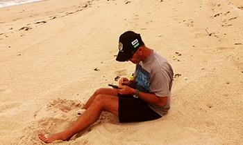 Chris sitting on beach injured