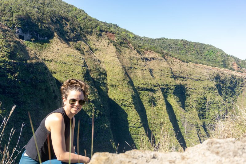 Woman standing in front of ridges while hiking in Kauai Hawaii