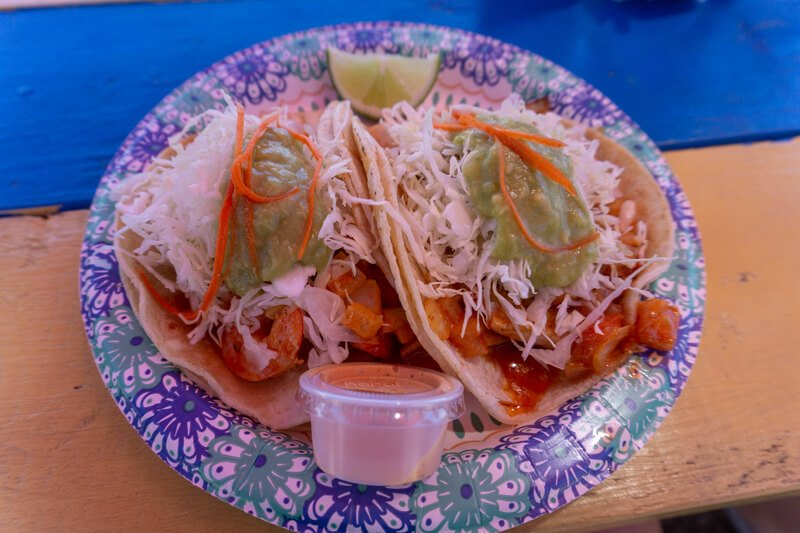 Two fish tacos on paper plate topped with shredded cabbage carrot and sauce with lime wedge and plastic hot sauce container on picnic table at El Rey Del Mar Kauai
