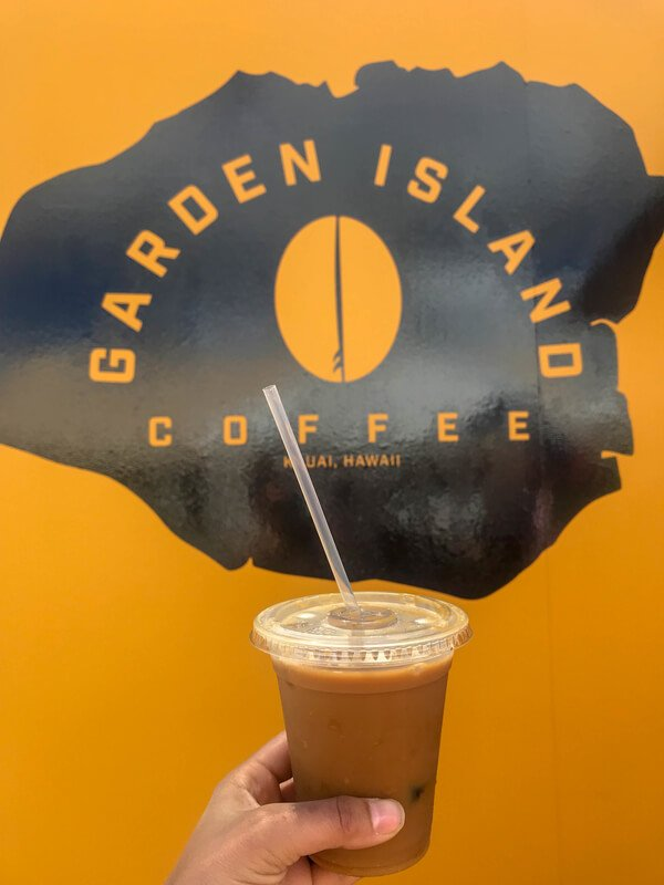 Hand holding plastic up iced coffee in front of garden island coffee truck logo